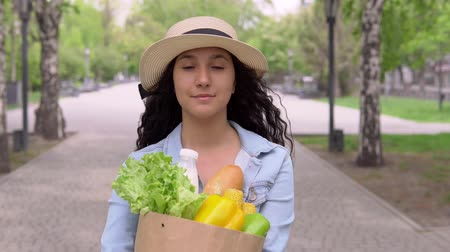 cash free : A young attractive woman in a denim jacket and hat carries a grocery bag while having a good mood and is smiling. 4K