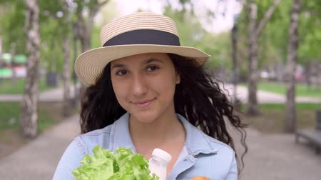 yeşillik : portrait of a beautiful girl carrying a package of fresh products with sunny weather having a good mood. 4K Stok Video