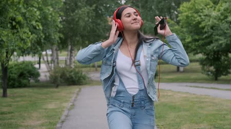 relance : Cheerful girl in red headphones jumps and listens to music Vídeos
