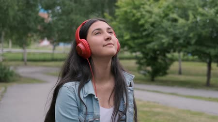 rejoices : beautiful cheerful girl dancing in the park listening to music on headphones. Fun mood