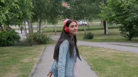 relance : Funny cheerful girl dancing in the park listening to music on headphones. Fun mood Vídeos