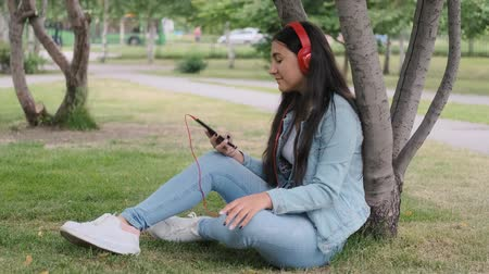 rejoices : girl listening to music in headphones sitting near a tree in the park.