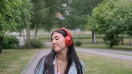 relance : Stylish cheerful girl dancing in the park listening to music on headphones Vídeos