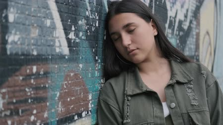 kadınlık : portrait of a young sad brunette hipster girl with brown eyes near a wall with graffiti Stok Video