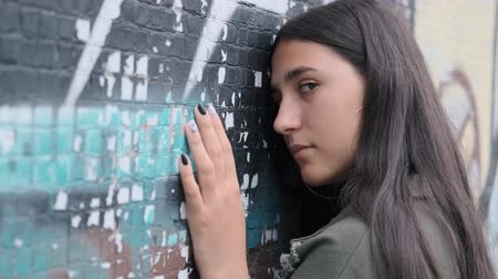 hiphop : sad young brunette girl stands with her hand down and leaning her head on the wall with graffiti turns to look at the camera and runs her hand down the wall Stock Footage
