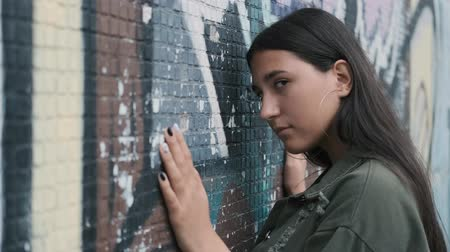 freckles : Beautiful hipster girl posing near the wall with graffiti. Hands on the wall