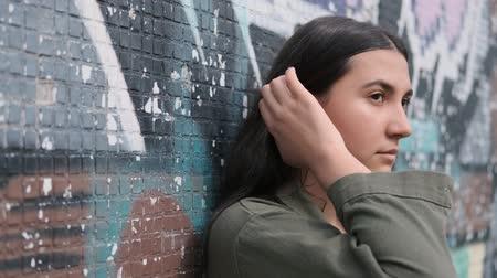 femininity : young beautiful thoughtful brunette girl stands near the wall with graffiti and runs her hand through her hair