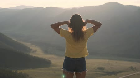raises : A young woman stands on the edge of a cliff and raises her hands up in front of the high rocky mountains during sunset. Happy girl enjoys success