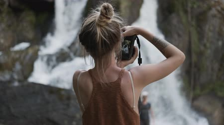 fotoğrafçı : Young paparazzi girl photographs a beautiful large waterfall standing on the stones in the jungle Stok Video