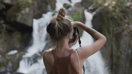 backpacken : A young paparazzi girl takes pictures of a beautiful large waterfall standing on stones in the jungle. Back view
