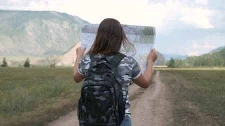 топография : Attractive woman tourist goes on the road with a map in his hands on a background of mountains. Back view.