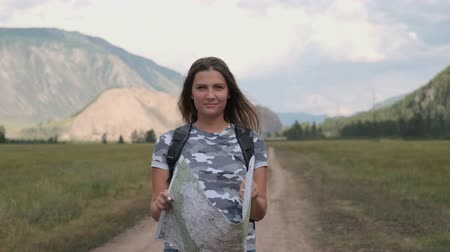 adultos : Beautiful woman tourist with a backpack goes on the road with a map in hands on a background of mountains. Travel concept Stock Footage