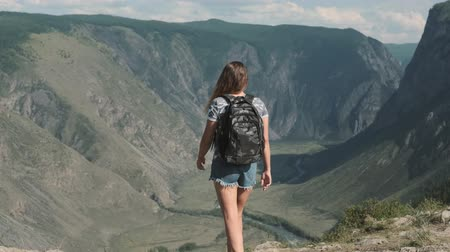 emelt : A female traveler with a rucksack climbs to the top of the mountain and raises his hands up feeling a sense of success and success. Stock mozgókép
