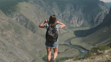 Çapraz kollar : A female traveler with a rucksack climbs to the top of the mountain and raises his hands up, feeling a sense of diving and success. Back view Stok Video