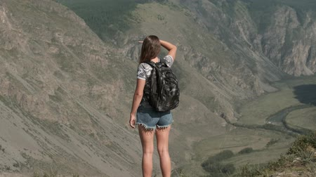 braços levantados : Female traveler with a rucksack stands on top of a mountain and looks ahead