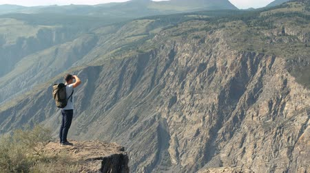 достигать : Happy male hiker comes to the edge of a cliff and looks forward. Overall plan.