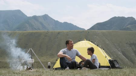tábor : Father and son are sitting near the tent and bonfire and laughing.