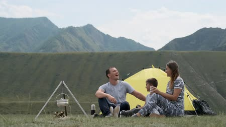 namiot : Happy family with a child laughing on campsite near a tent with a bonfire. Wideo