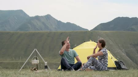 hozzábújva : Loving couple relax and have fun outdoors in front of the tent in sunny weather. Stock mozgókép
