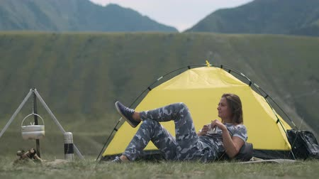 namiot : Girl tourist resting lying in front of a tent with a mug of tea on a background of mountains