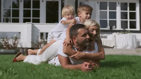 Happy family with children having fun lying on each other near the house on the grass