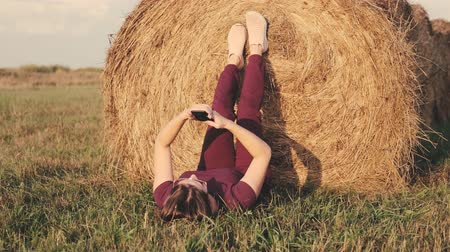 palheiro : A woman with a smartphone lies in a field next to a haystack. Stock Footage