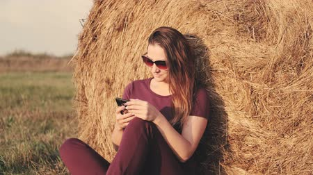 palheiro : A woman with a smartphone sits in a field next to a haystack.