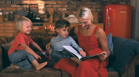 biblia : Beautiful mother reads a book to two sons sitting on a sofa against the background of the kitchen and smiling boy with blond hair laughs, cheerful and happy family spends the evening together