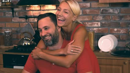 összejövetel : Beautiful blonde hugs her husband in the kitchen and smiles