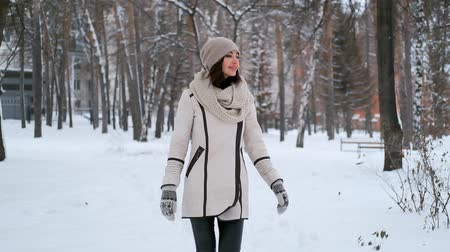 портфель : beautiful young woman is walking in the park in winter and smiling