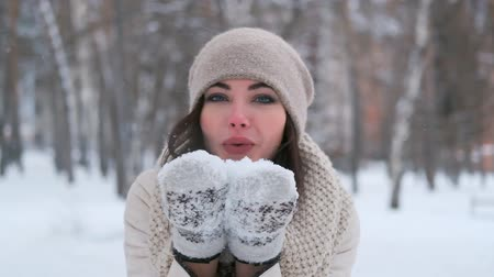 background young : attractive young woman in a winter forest in a good mood blows off snow from mittens and smiles. slow motion