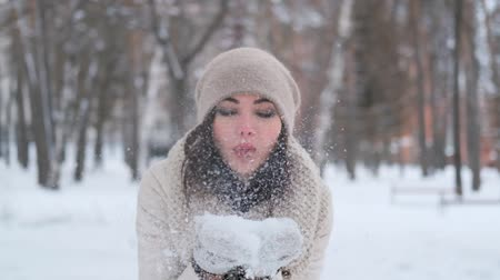 levegős : attractive young woman in a winter forest in a good mood blows off snow from mittens smiling and then throws snow up. slow motion Stock mozgókép