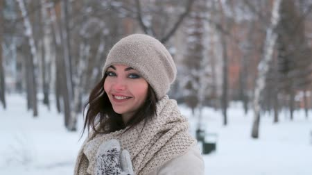 attractive young woman in a winter forest in a good mood whirls and smiles while looking at the camera. slow motion