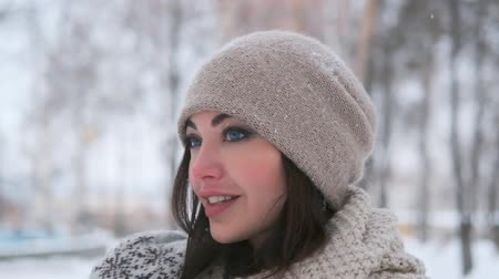 imbibe : portrait of a beautiful girl in a hat with dark hair stands in the winter in the park in snowy weather and smiles cute.slow motion