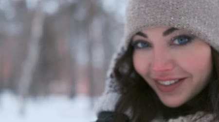 portrait of a beautiful girl with blue eyes posing in a winter park in a good mood. close-up