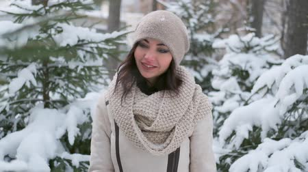 a beautiful young woman in a good mood walks through the winter forest, looks at the Christmas trees in the snow and smiles. slow motion Filmati Stock