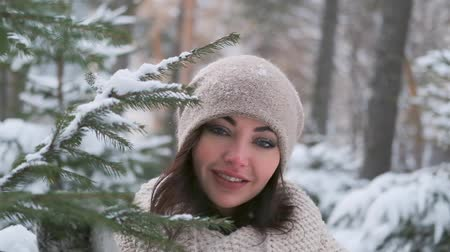 encantador : portrait of a beautiful young girl in a winter park near the Christmas tree. slow motion