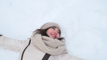 snow angel : An attractive young blue-eyed woman in a winter forest lies on the snow and waves her hands, then looks at the camera and smiles. slow motion