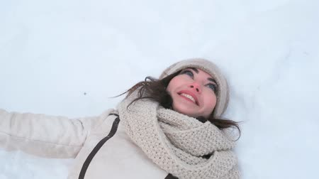 akciók : attractive young blue-eyed woman in the winter forest lies on the snow waves her hands catches snow and rejoices. close-up. slow motion