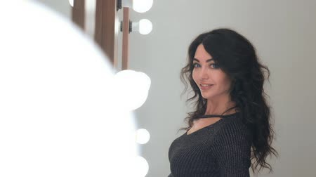 брюнет : portrait of a stylish woman with beautiful professional hair styling posing standing in front of a mirror with light bulbs in a beauty salon. slow motion