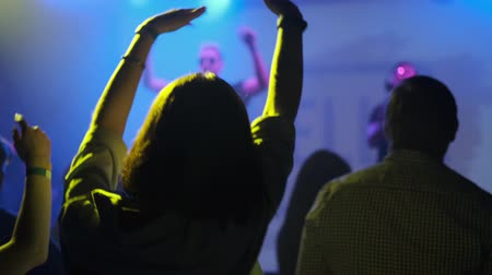 Girl waving her hands during a performance of artists on stage with a light show Stock Footage