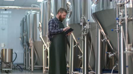 A male brewer with a beard checks the readings of devices on beer tanks using a tablet. Craft beer production