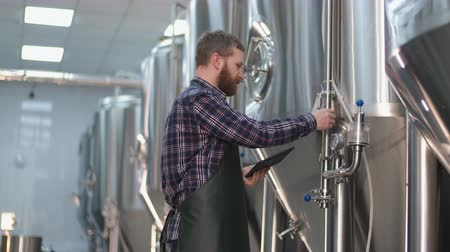 Brutal Male brewer with a beard is standing near the beer tanks and captures the readings using a tablet. Craft beer production