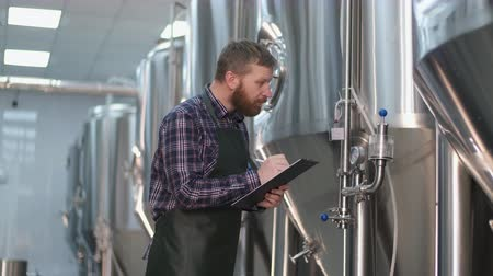 A male brewer in an apron with a beard stands near the beer tanks and writes down the readings. Craft beer production