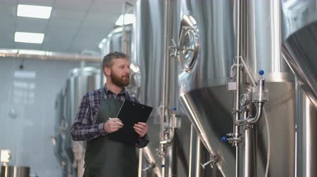 A male brewer in an apron with a beard comes to the beer tanks and writes down the readings. Craft beer production Stock Footage