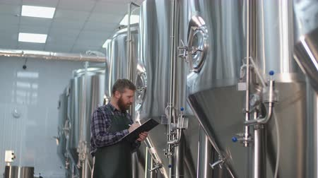 A male brewer in an apron with a beard walks through the beer factory and records the readings on beer tanks. Production of craft beer Stock Footage