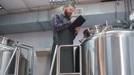 A male brewer in an apron with a beard is standing near the beer brewing tank and is taking readings. Production of craft beer