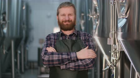 Portrait of businessman male brewer with beard looking at the camera and smiling while standing at a beer factory