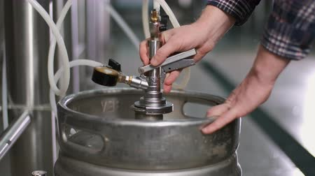 A male brewer connects a keg to a beer tank and fills it with beer. Close-up.