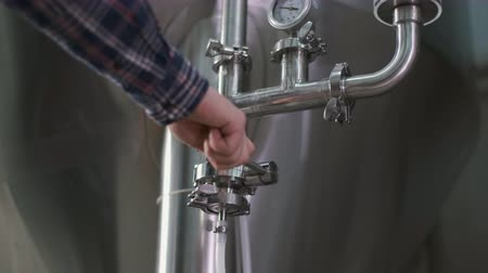 Close-up of a male brewer opening a tap for brewing beer from a beer tank to a keg.